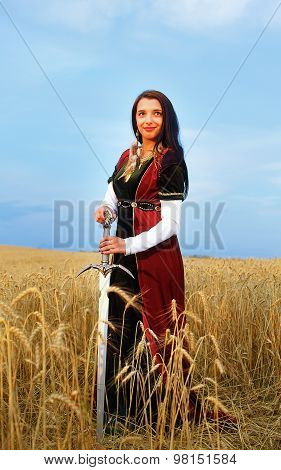 The beautiful girl with a sword. Natural background.