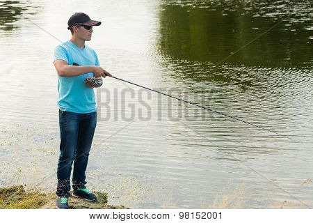A fisherman with a fishing rod on the river bank.