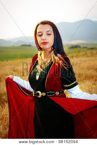 young woman with dark hair, green and red velvet historical dress and gold jewel and a subtle smile.