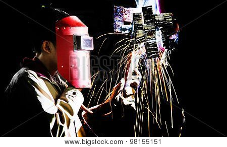 Man With Protective Mask Welding Metal And Sparks