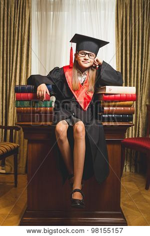 Little Girl In Graduation Cap Posing On Table At Library