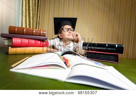 Thoughtful Girl In Graduation Cap Dreaming While Sitting At Table