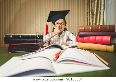 Girl Wearing Eyeglasses And Graduation Cap Posing At Desk