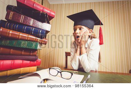 Amazed Smart Girl In Graduation Cap Looking At Big Heap Of Book