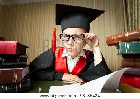 Funny Girl In Graduation Cap And Eyeglasses Looking At Camera