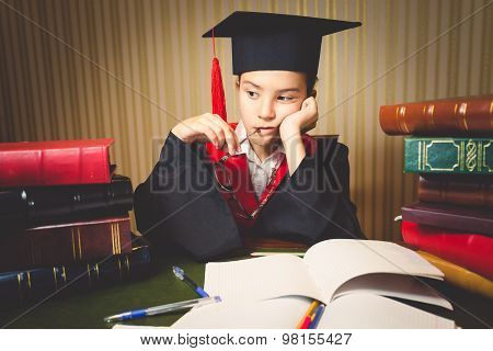 Toned Portrait Of Thoughtful Smart Girl In Graduation Hat And Gown