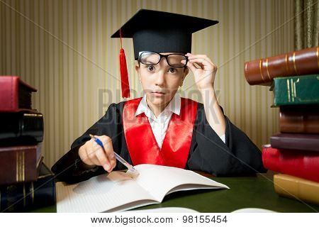 Portrait Of Smart Girl In Graduation Clothes Doing Homework