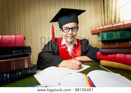 Smiling Girl In Graduation Cap Sitting At Table Between Pile Of Book