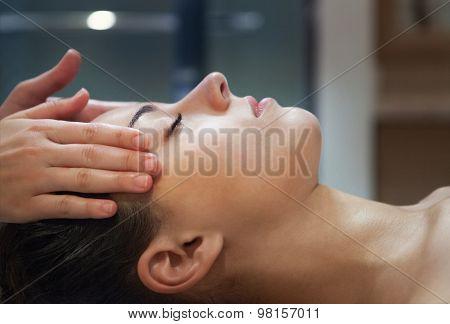 Masseur Doing Facial Massage Of An Adult Woman