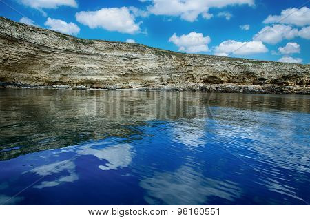 Seascape, Rocks Against A Blue Sky With Clouds