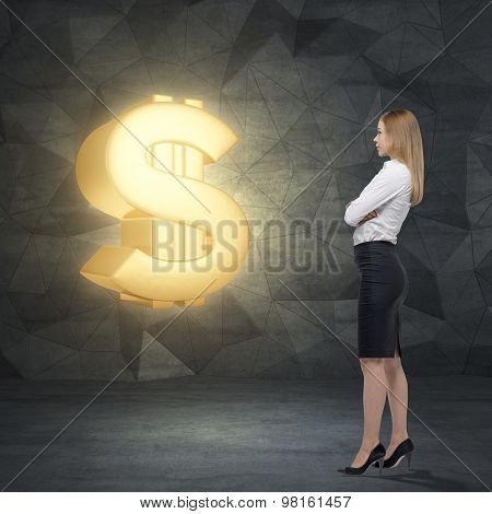 Side View Of Young Business Lady Who Is Looking At The Huge Golden Dollar Sign. Contemporary Backgro