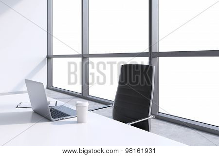 A Workplace With Laptop And Coffee Cap In A Modern Panoramic Office, Copy Space In Windows. A Concep