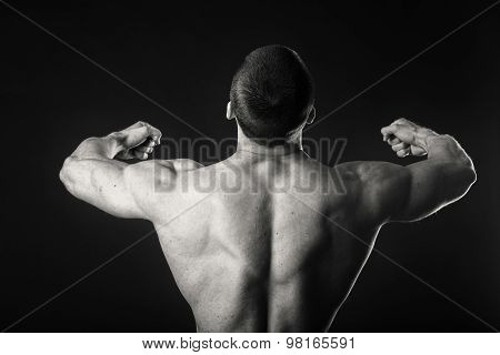 Man posing on a black background, shows his muscles