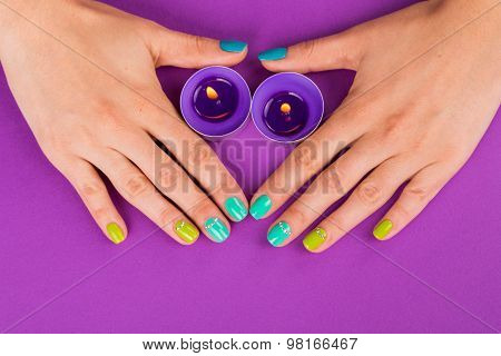 Beautiful manicure on purple background.