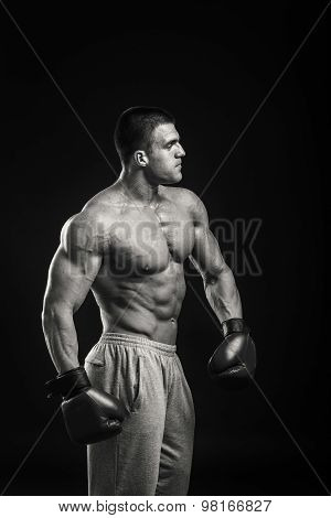 Young Boxer fighter over black background. Boxing man ready to fight