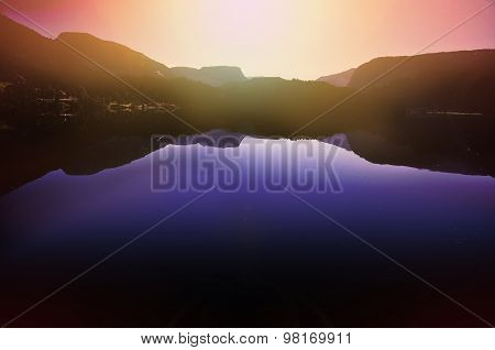 Sunset Over Tranquil Water And Mountains