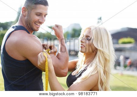 Blonde Woman Measure Mans Biceps