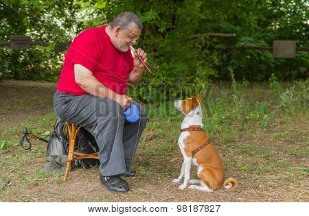 Man plays his basenji dog a melody with fife