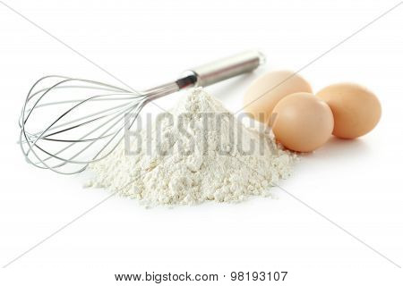Heap Of Wheat Flour With Eggs And Whisk Isolated On White