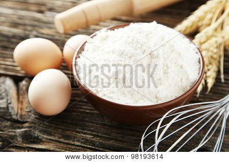 Bowl Of Wheat Flour With Eggs And Whisk On Brown Wooden Background
