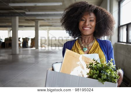 Confident businesswoman carrying a box to her new office