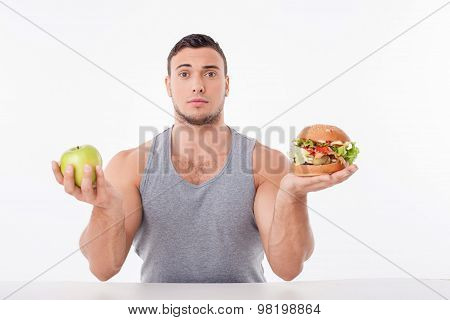Cheerful young man is making decisions about food