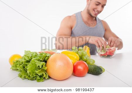 Cheerful young man is cooking healthy food