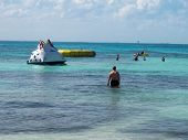 picture of ski-doo  - children play on a raft climber in the ocean while other people wade swim and enjoy - JPG