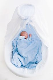 stock photo of bassinet  - Newborn baby boy in bed - JPG