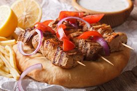stock photo of souvlaki  - Greek souvlaki kebab with pita bread and vegetables close - JPG