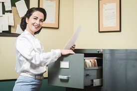 stock photo of secretary  - Smiling vintage secretary searching files in the filing cabinet drawers - JPG