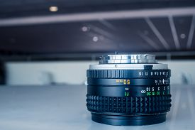 pic of inverted  - A 50mm prime lens placed inverted on a white table - JPG
