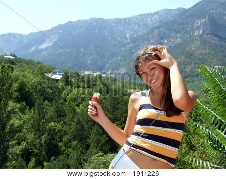 The Smiling Young Beautiful Girl On A Background Of Mountains