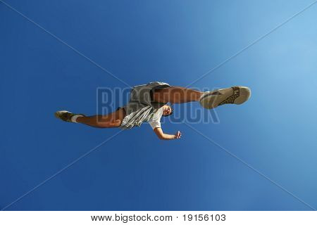 young man jumping over camera over blue sky