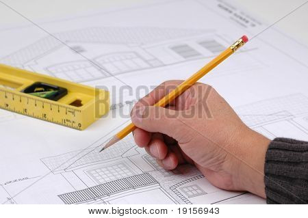 Hand and pencil on blue print with level on background