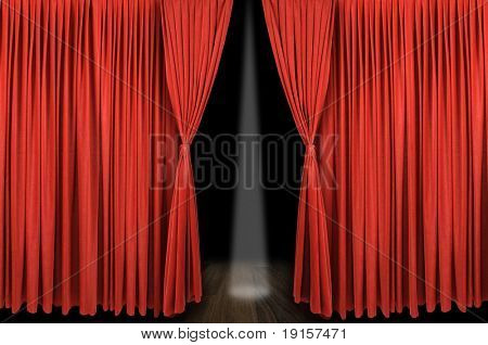 Large red curtain stage opening with dark background and spot light