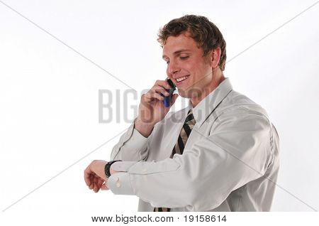 Young businessman on the cell phone looking at his watch against a white background