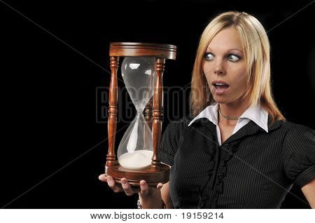 Woman holding a sand timer expressing panic isolated on a black background