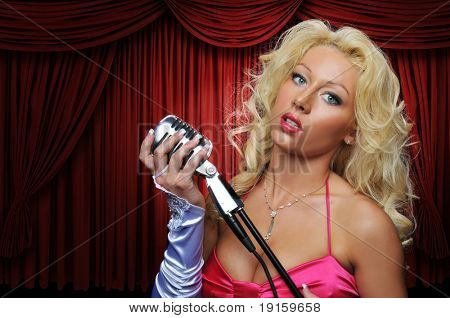 Singer with vintage microphone on stage with red curtain and spot light
