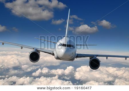 Commercial airliner in flight with clouds on the background
