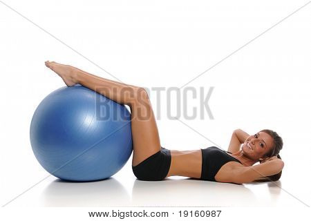 Young woman working out with a ball isolated on a white background