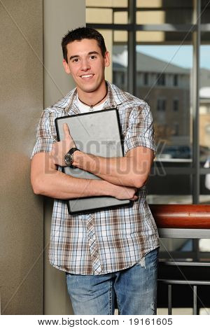 Young man holding his laptop computer with college buildings as background