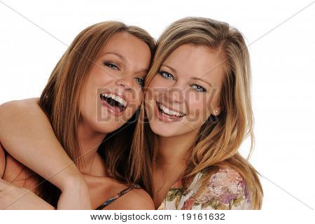 Two Young beautiful Sisters smiling isolated on a white background