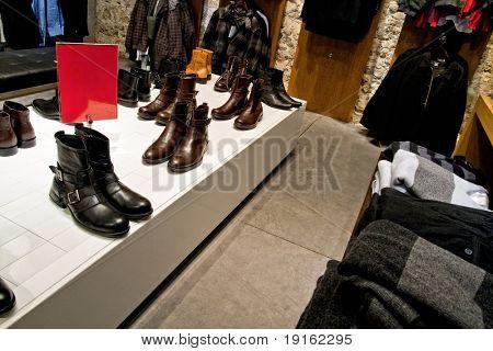 Muchos zapatos y ropa en los estantes de las tiendas