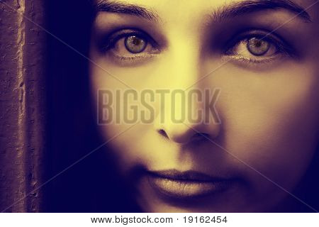 Artistic portrait of mysterious young woman with spooky eyes
