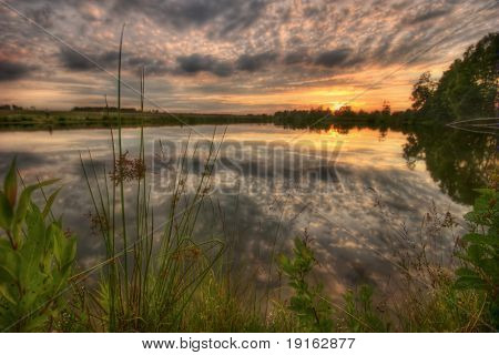 Gloomy sunset around lake. It is photographed in Russia. 60 kilometers from Moscow. The end of summer.
