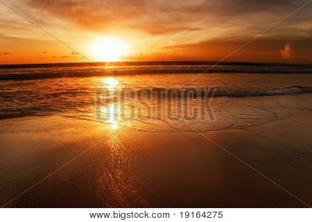 Sunset on the tropical beach. Legian beach on Bali island. Indonesia