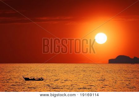 Lonely boat in the sea under sunset sky
