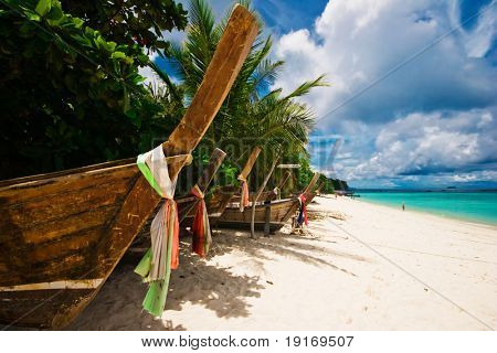 Old boats on the white sand tropical beach. Andaman sea. Province Krabi. Koh Phi Phi island. Kingdom Thailand