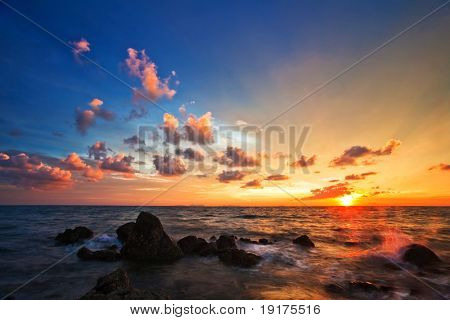 Tropical sunset on the stones beach. Lanta island. Thailand